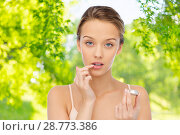 Купить «young woman applying lip balm to her lips», фото № 28773386, снято 31 октября 2015 г. (c) Syda Productions / Фотобанк Лори