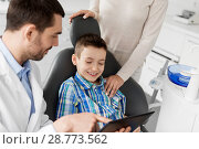 Купить «dentist showing tablet pc to kid at dental clinic», фото № 28773562, снято 22 апреля 2018 г. (c) Syda Productions / Фотобанк Лори