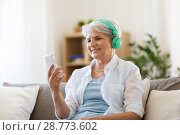 Купить «senior woman in headphones listening to music», фото № 28773602, снято 24 мая 2018 г. (c) Syda Productions / Фотобанк Лори