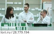 Купить «Positive team of pharmacists looking at camera at the hospital pharmacy», видеоролик № 28779194, снято 6 апреля 2017 г. (c) Vasily Alexandrovich Gronskiy / Фотобанк Лори