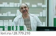 Купить «Portrait of senior pharmacist smiling and talking to a camera», видеоролик № 28779210, снято 6 апреля 2017 г. (c) Vasily Alexandrovich Gronskiy / Фотобанк Лори