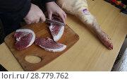 Мужчина разделывает свиную ногу с помощью ножа. Стоковое видео, видеограф Олег Хархан / Фотобанк Лори