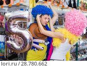 Купить «Family couple preparing for fest and choosing clown wigs», фото № 28780662, снято 11 апреля 2017 г. (c) Яков Филимонов / Фотобанк Лори