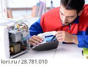 Купить «Man repairman repairing iron at service center», фото № 28781010, снято 11 июля 2017 г. (c) Elnur / Фотобанк Лори