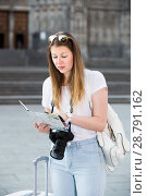 Купить «Young cheerful traveling girl using paper map», фото № 28791162, снято 17 мая 2017 г. (c) Яков Филимонов / Фотобанк Лори