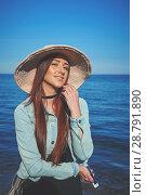 Купить «Redhead girl wearing black dress and jeans jacket. Straw hat. Holding smartphone. Woman standing on sand. Retro toned image.», фото № 28791890, снято 28 апреля 2018 г. (c) Вдовиченко Денис / Фотобанк Лори