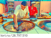 Russia, salt-Iletsk, August 2017: a man cook in a cafe cooks a lot of pilaf in a large vat. Редакционное фото, фотограф Акиньшин Владимир / Фотобанк Лори
