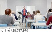 Купить «Smiling male teacher giving presentation for students in lecture hall», видеоролик № 28797970, снято 21 мая 2018 г. (c) Яков Филимонов / Фотобанк Лори