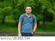 Купить «Smiling young man standing relaxed on a green lawn at a summer park.», фото № 28803734, снято 28 июня 2018 г. (c) Иван Карпов / Фотобанк Лори
