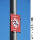 Купить «Перечеркнутый силуэт дрона-беспилотника и надписи на английском: «No fly zone» и на русском «Бесполетная зона» на территории природно-ландшафтного парка «Зарядье» в Москве», эксклюзивное фото № 28804418, снято 2 июля 2018 г. (c) lana1501 / Фотобанк Лори
