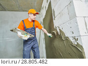 Купить «Renovation at home. Plasterer spreading plaster on wall.», фото № 28805482, снято 31 марта 2018 г. (c) Дмитрий Калиновский / Фотобанк Лори