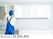 Купить «kitchen furniture set installation. hanging cabinet», фото № 28805494, снято 1 апреля 2018 г. (c) Дмитрий Калиновский / Фотобанк Лори