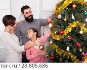 Купить «Family decorating tree», фото № 28805686, снято 21 сентября 2018 г. (c) Яков Филимонов / Фотобанк Лори