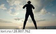 Купить «Silhouette of young woman doing morning warm-up on the riverside at sunrise», видеоролик № 28807762, снято 17 октября 2018 г. (c) Константин Шишкин / Фотобанк Лори