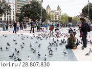 Купить «Туристы на площади Каталонии в Барселоне кормят голубей и фотографируют их. Испания», фото № 28807830, снято 7 апреля 2018 г. (c) Наталья Волкова / Фотобанк Лори