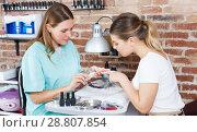 Купить «Woman polishing nails to female client in modern beauty salon», фото № 28807854, снято 30 мая 2018 г. (c) Яков Филимонов / Фотобанк Лори