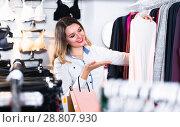 Купить «Female is choosing pretty long sleeve shirt», фото № 28807930, снято 20 марта 2017 г. (c) Яков Филимонов / Фотобанк Лори