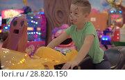 Купить «A boy in a game zone on a motorcycle simulator», видеоролик № 28820150, снято 15 декабря 2018 г. (c) Данил Руденко / Фотобанк Лори
