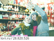 Купить «Smiling girl with woman are buying toys for X-mas tree», фото № 28820526, снято 19 декабря 2017 г. (c) Яков Филимонов / Фотобанк Лори