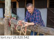 Купить «Smiling man farmer with girth standing at stable outdoor», фото № 28820542, снято 4 июля 2018 г. (c) Яков Филимонов / Фотобанк Лори