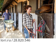 Купить «Smiling woman standing near horse at stable outdoor at summer day», фото № 28820546, снято 4 июля 2018 г. (c) Яков Филимонов / Фотобанк Лори