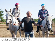 Купить «Positive mature couple with jockey learn to riding horse at farm», фото № 28820610, снято 26 сентября 2018 г. (c) Яков Филимонов / Фотобанк Лори