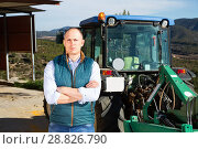 Купить «Confident male owner of vineyard posing near tractor outdoors in», фото № 28826790, снято 22 января 2018 г. (c) Яков Филимонов / Фотобанк Лори