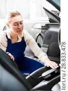 Купить «Female mechanic metering color of car upholstery», фото № 28833478, снято 4 апреля 2018 г. (c) Яков Филимонов / Фотобанк Лори