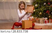Купить «happy girl opening christmas gift at home», видеоролик № 28833738, снято 26 июля 2018 г. (c) Syda Productions / Фотобанк Лори