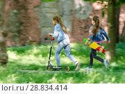 Купить «Девочка весело едет на самокате, за ней бежит другая девочка со скейтом в руках», фото № 28834414, снято 6 июля 2020 г. (c) Иванов Алексей / Фотобанк Лори
