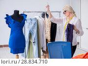 Купить «Woman tailor working on new dress designs», фото № 28834710, снято 13 апреля 2018 г. (c) Elnur / Фотобанк Лори