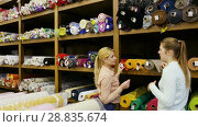 Купить «Polite female seller helping young woman in choice of interesting cloth in textile shop», видеоролик № 28835674, снято 28 марта 2018 г. (c) Яков Филимонов / Фотобанк Лори