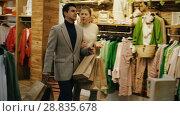 Купить «Couple is satisfied shopping and walking with package in the clothes store.», видеоролик № 28835678, снято 27 марта 2018 г. (c) Яков Филимонов / Фотобанк Лори