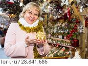 Купить «female on shiny tinsel choosing candle», фото № 28841686, снято 27 ноября 2017 г. (c) Яков Филимонов / Фотобанк Лори