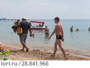 Купить «Продавец рыбы идёт по центральному пляжу курортного города Евпатория, Крым», фото № 28841966, снято 29 июня 2018 г. (c) Николай Мухорин / Фотобанк Лори