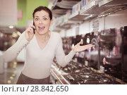Купить «Woman with phone choosing hob in store», фото № 28842650, снято 21 февраля 2018 г. (c) Яков Филимонов / Фотобанк Лори