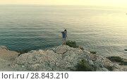 Купить «Man with backpack standing on the rock», видеоролик № 28843210, снято 16 июля 2018 г. (c) Илья Шаматура / Фотобанк Лори