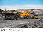 Купить «Large quarry dump truck. Loading the rock in dumper. Loading coal into body truck. Production useful minerals. Mining truck mining machinery, to transport coal from open-pit as the coal production.», фото № 28843670, снято 22 июня 2018 г. (c) Сергей Тимофеев / Фотобанк Лори