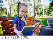 Купить «Девочка увлечена книгой сидя в парке на скамеке», фото № 28843902, снято 7 июля 2018 г. (c) Иван Карпов / Фотобанк Лори