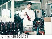 Купить «Young man holding newly produced bottle of wine», фото № 28860158, снято 21 сентября 2016 г. (c) Яков Филимонов / Фотобанк Лори