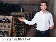 Купить «Male wine maker showing bottles on winery», фото № 28860174, снято 21 сентября 2016 г. (c) Яков Филимонов / Фотобанк Лори