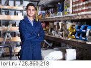 Adult man in uniform is standing near shelving. Стоковое фото, фотограф Яков Филимонов / Фотобанк Лори