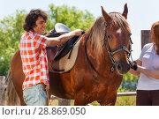 Купить «Young man and woman saddling chestnut brown horse», фото № 28869050, снято 2 июля 2016 г. (c) Сергей Новиков / Фотобанк Лори
