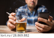 Купить «man with cellphone drinking alcohol and smoking», фото № 28869882, снято 24 ноября 2017 г. (c) Syda Productions / Фотобанк Лори