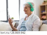senior woman in headphones listening to music. Стоковое фото, фотограф Syda Productions / Фотобанк Лори