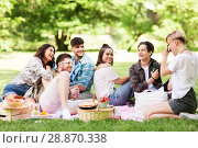 Купить «friends photographing at picnic in summer park», фото № 28870338, снято 17 июня 2018 г. (c) Syda Productions / Фотобанк Лори