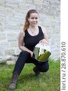 Купить «Portrait of girl with motorcycle helmet looking at the camera, sitting on grass near wall», фото № 28870610, снято 16 июня 2018 г. (c) Кекяляйнен Андрей / Фотобанк Лори