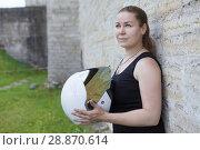 Купить «Motorbiker woman standing back to stone wall, holding white helmet in hand», фото № 28870614, снято 16 июня 2018 г. (c) Кекяляйнен Андрей / Фотобанк Лори