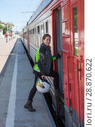 Купить «Motorcyclist woman stepping in railway carriage for trip without vehicle, transit», фото № 28870622, снято 16 июня 2018 г. (c) Кекяляйнен Андрей / Фотобанк Лори