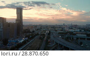 Купить «Flight of the camera over the high-rise buildings, traffic and lights of cars on multi-lane highways. Bright blood red sunset over the city and dramatic clouds and road junction in Moscow», видеоролик № 28870650, снято 29 июля 2018 г. (c) Mikhail Starodubov / Фотобанк Лори
